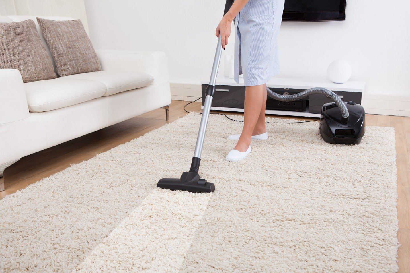 Cropped image of young maid cleaning carpet with vacuum cleaner at home